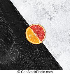 Grapefruit and orange citrus fruit halves on wooden...