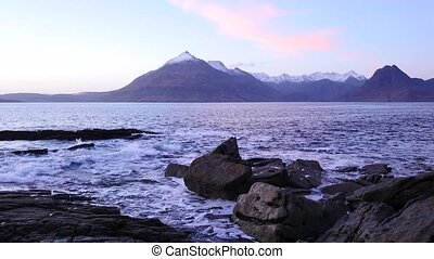Evening in Elgol bay on west coast of the Isle of Skye in Scotland during an windy sunset . Snowy mountains on Soay island above sea of the Hebrides, waves crashing against to boulders and sharp rock