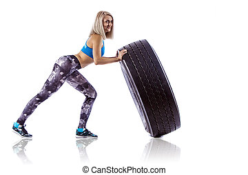 Young fitness woman execute exercise with large tire casing....