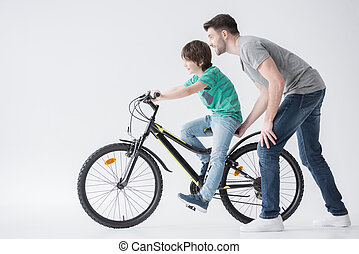 father helping son to ride bicycle on white