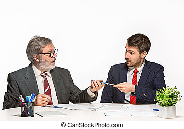 The two colleagues working together at office on white background.