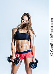 Young beautiful fitness woman posing in studio