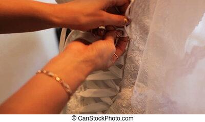 The best man tying white bride