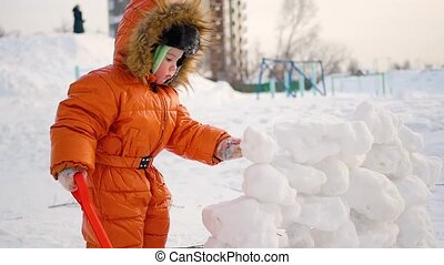 child playing outdoors in winter. The child builds a wall of snow stones