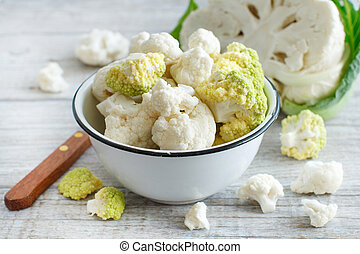 Fresh raw cauliflower in a bowl on an old wooden table