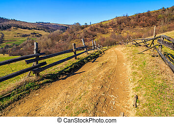 wooden fence along the path in mountains - Spring time rural...