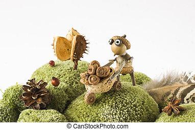 little garden helper with handcart harvesting acorns autumn...