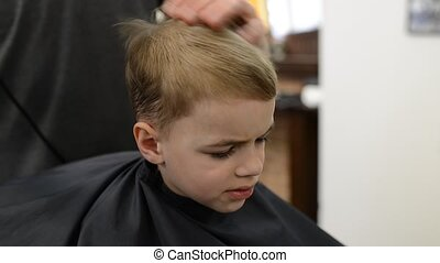 Boy six years old in barbershop. Happy little boy in beauty...