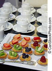Pastries with fruit and coffee cups, breakfast