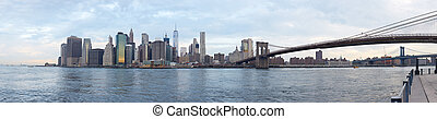 New York city skyline and Brooklyn Bridge in a cloudy day