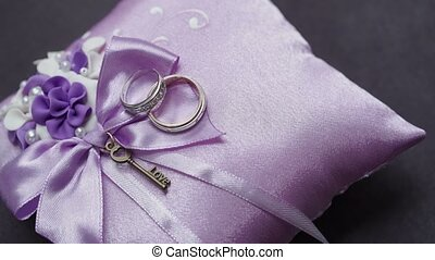 Wedding rings on purple pillow
