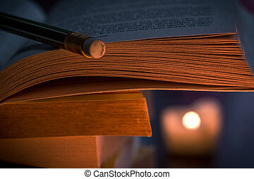 book and pencil in candle light