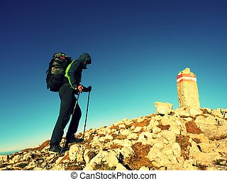 Tourist with poles and backpack walk to mountain peak. Last...