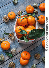 the fruits of fezalis and orange tangerines with leaves and...