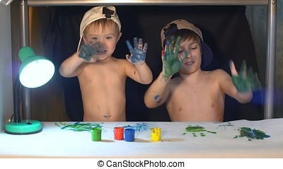Happy kids playing with finger paints.