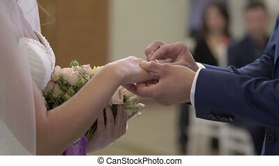 Wedding ceremony: groom puts a ring on bride hand shot