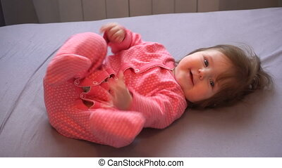 Little cute baby girl laughting playing with mom