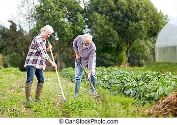 senior couple with shovels at garden or farm - farming,...