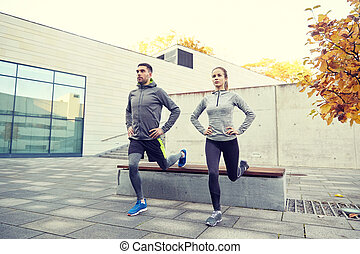 couple doing lunge exercise on city street - fitness, sport,...