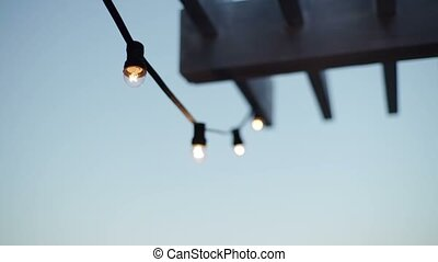 Lamp garland on roof at the evening