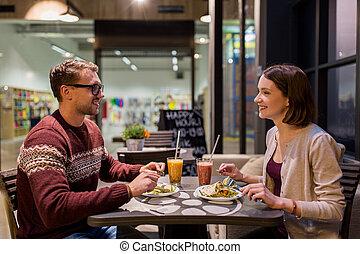 happy couple eating dinner at vegan restaurant