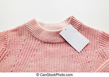 close up of sweater or pullover with price tag - clothes,...