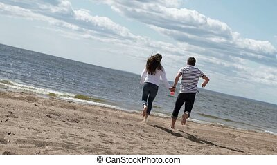 Young lovely couple running on a beach and holding hands