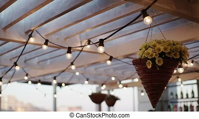 Lamp garlands on roof at the evening