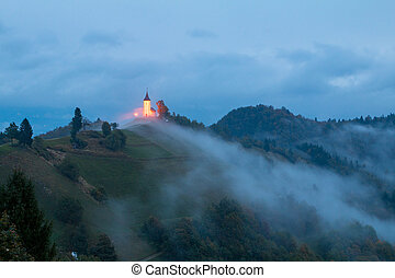 Jamnik church on a hillside in autumn, foggy weather at...