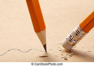 pencil draws a wavy line on paper and pencil rubber eraser...