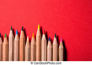 line of colored pencils on bright red background. Creative...