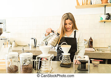 Pretty female barista brewing coffee - Good looking young...