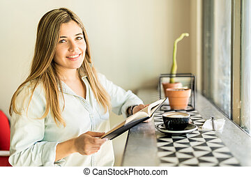 Cute girl enjoying coffee and reading - Portrait of a...