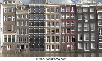Dutch houses on waterside, Amsterdam - Panning shot of...