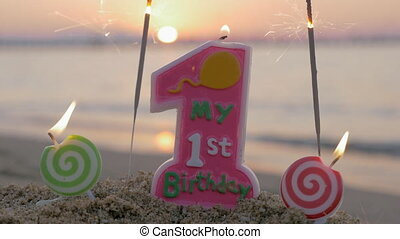 Baby girl first birthday candle on the beach - Close-up shot...