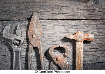 Old locksmith tools on a gray and cracked wooden background....