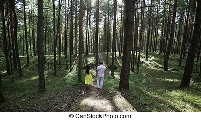 Young lovely couple walking in forest at sunny day