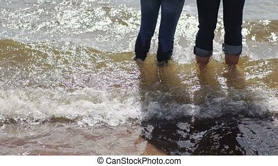 Young lovely couple staying in water in jeans