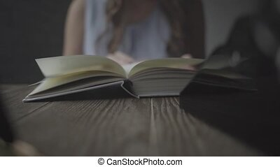 Girl leafing through a book closeup.