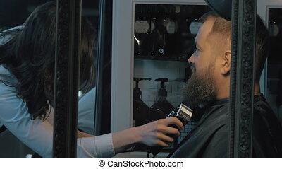 Trimming beard in barbershop - Woman barber trimming beard...