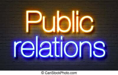Public relations neon sign on brick wall background.