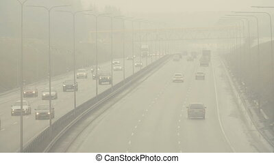 Automobiles cars drive on foggy city road. Dangerous driving conditions in winter season.