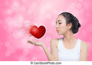 Woman celebrating Valentines day blowing red heart with...