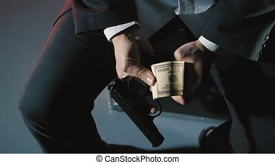 close-up hands of a dangerous man with a gun counts the...