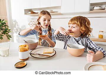 Lively cute girl making a sandwich for her brother - Just...