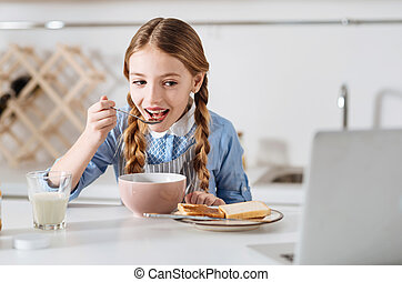 Curious little girl watching a video while having breakfast...