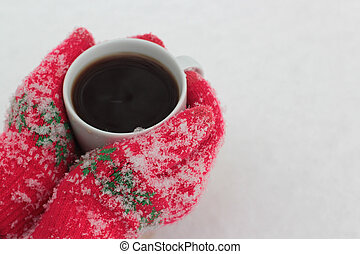 hands hold a cup of coffee against the background of snow