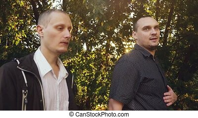 Young handsome men have a serious talk while walking in the...