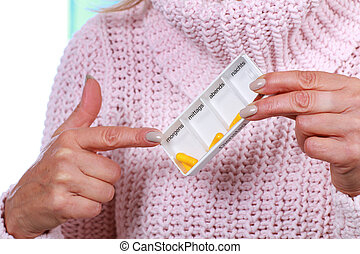 Mature woman with pill box - Mature woman points on tablet...