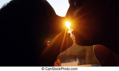 Romantic young couple silhouette is kissing on a sunset with...